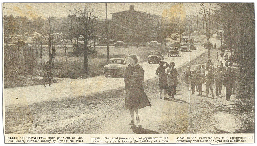 Black and white photograph from a newspaper clipping, published in The Evening Star on April 24, 1955. The caption reads: Filled to capacity. Pupils pour out of Garfield School, attended mostly by Springfield, Virginia pupils. The rapid jumps in school population in the burgeoning area is forcing the building of a new school in the Crestwood section of Springfield and eventually another in the Lynbrook subdivision. The picture was taken east of the school on Old Keene Mill Road. The road is barely wide enough to fit two cars. It was taken before all the shopping centers in this area were built and much of the surrounding area is still forest. Groups of children walk along a dirt path toward Backlick Road. One student is riding his bicycle up the street, followed by a long line of cars pulling out of the school's driveway.