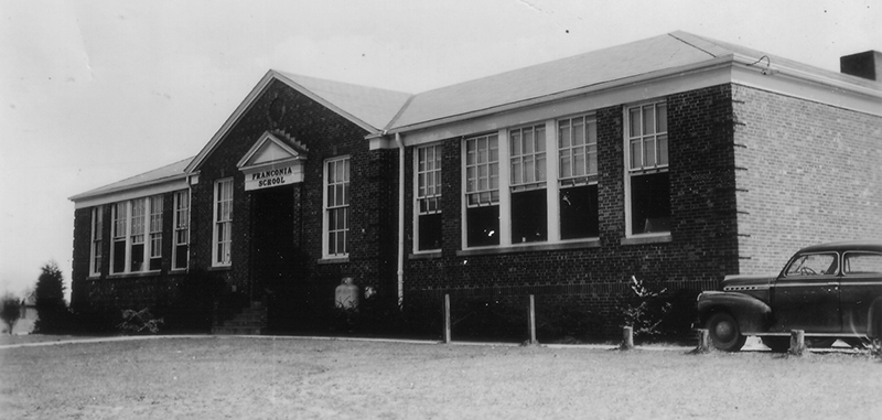 Black and white photograph of the original main entrance of Franconia Elementary School taken in 1942 for the Fairfax County School Board's Fire Insurance Survey. A late 1930s-era car is visible to the right.