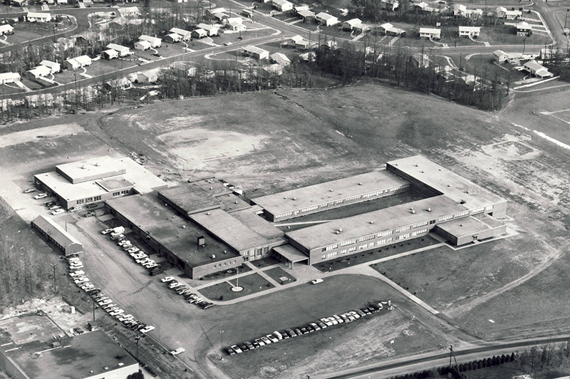 Black and white aerial photograph of Washington Irving Intermediate School taken during the 1960s. The L-shaped building is much smaller than it is today. Visible in the distance are the newly built homes along Old Oaks Drive and Greeley Boulevard.