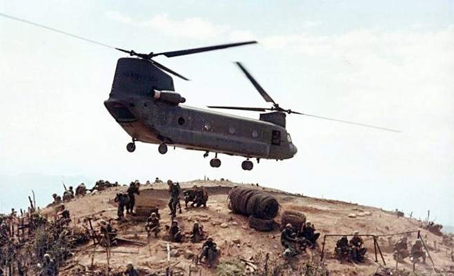 Color photograph of a United States Army CH-47 Chinook helicopter, pictured in flight above a hilltop in Vietnam. There are soldiers encamped on the hilltop. The helicopter has two sets of rotors and is painted a dark grey or green.