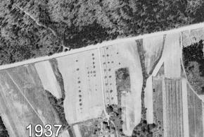 Black and white aerial photograph of Garfield Elementary School taken in 1937. Only one building is visible, a lone house south of the school site. This is the house that will be torn down and replaced by the tennis courts. It is reached by a long driveway leading directly from Old Keene Mill Road through the middle of the future site of the school. The area around the house is all farmland and the land on the opposite side of the road is a thick forest.