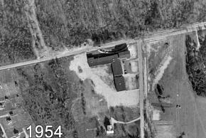 Black and white aerial photograph of Garfield Elementary School taken in 1954. There are cars parked in the front driveway loop facing Old Keene Mill Road. Old Keene Mill Road is only two-lanes wide. The Methodist church has not been built yet. Across the road from the school, in the area that will become the shopping center, is a thick forest.