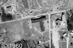 Black and white aerial photograph of Garfield Elementary School taken in 1960. The entire south wing of the building is missing. The main entrance appears to be a driveway loop that fronts Old Keene Mill Road. The shopping centers across the road are in development. The ground is bare earth and no buildings are visible. In the previous photograph there was a tennis court south of the school. The court is gone and a house stands in that spot. The Methodist church parking lot is unpaved.