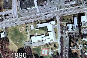 Color aerial photograph of Garfield Elementary School taken in 1990. The building layout looks much the same as it did before except there are no mobile classrooms outside. There are construction trailers present near the building close to Old Keene Mill Road, but renovation work does not appear to be happening on the outside of the building.