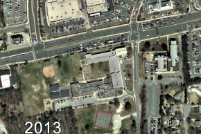Color aerial photograph of Garfield Elementary School taken in 2013. The wing on the west side of the building has not been constructed yet, so the building is U-shaped. Its roof is painted several shades of grey. The central courtyard connects to the playground. There are three mobile classrooms stationed in the rear of the building.